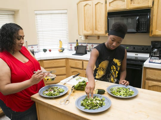 Keisha Tatem and her daughter Madison Tatem, 15, prepare a salad in the kitchen of their home in Chandler.