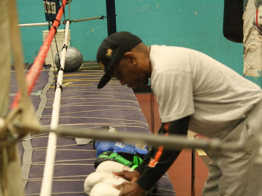 """Daryl """"P-man"""" Jones sets up boxing gloves for a group of kids he trains daily at the Findlay Street Neighborhood House. Jones also helped bring the USA Boxing Regional Silver Gloves tournament to Cincinnati."""