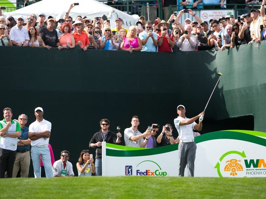 Tiger Woods watches his tee shot on the 17th hole while