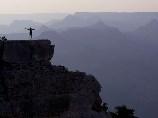 A tourist takes in the view of the layered buttes and