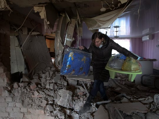 A resident carries out belongings from an apartment