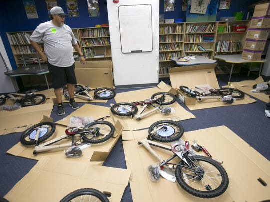 Volunteer Mark Gonzales looks at bikes to be built