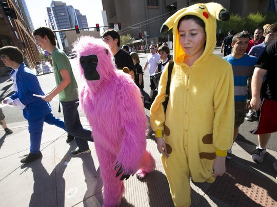 "Dressed as a pink gorilla, Cecilia Siqueiros, 16, of Mesa and Jennifer Escalante, 17, of Phoenix dressed as ""Pikachu"" from ""Pokemon""  cross Washington Street in downtown Phoenix on the way to the Convention Center for Phoenix Comicon on June 5. 2014."