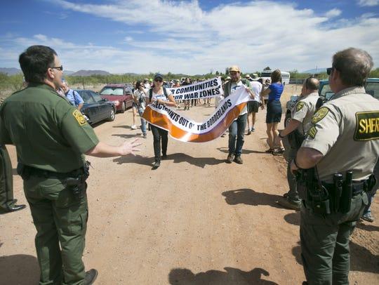 Protesters walk toward Border Patrol agents and Pima