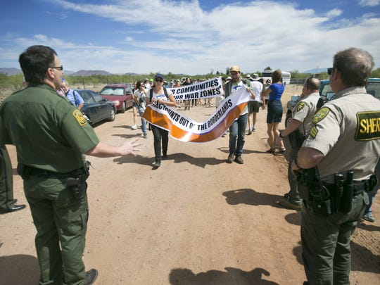 Protesters walk toward Border Patrol agents and Pima County Sheriff's Deputies at the Border Patrol checkpoint on Arivaca Road in Amado on Wednesday, May 27, 2015. Around 75 protesters rallied to have the checkpoint shut down.