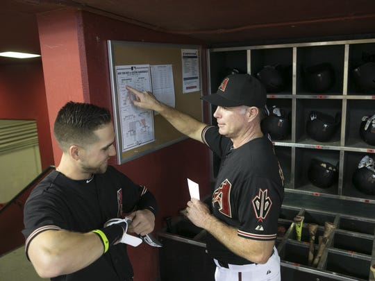 Diamondbacks coach Glenn Sherlock looks at the Diamondbacks lineup card while talking to Diamondbacks outfielder Ender Inciarte in the dugout before the major league baseball game against the Mets at Chase Field in Phoenix on Saturday, June 6, 2015.