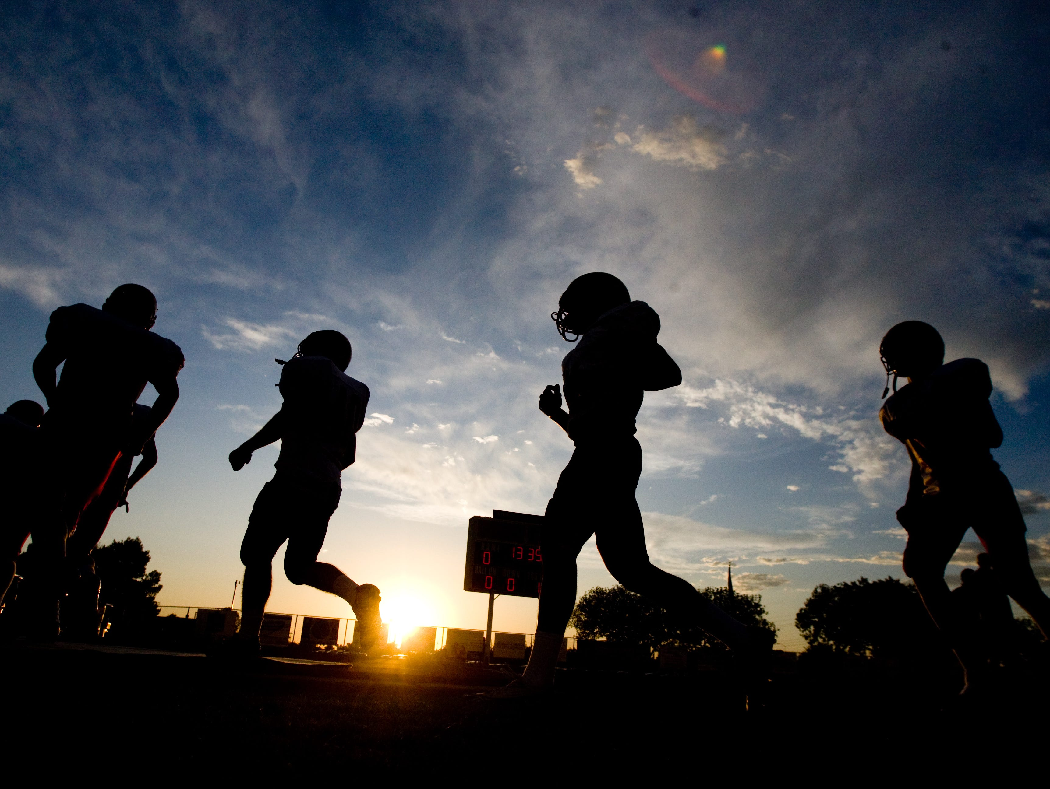 High school football players practice in the summer heat.