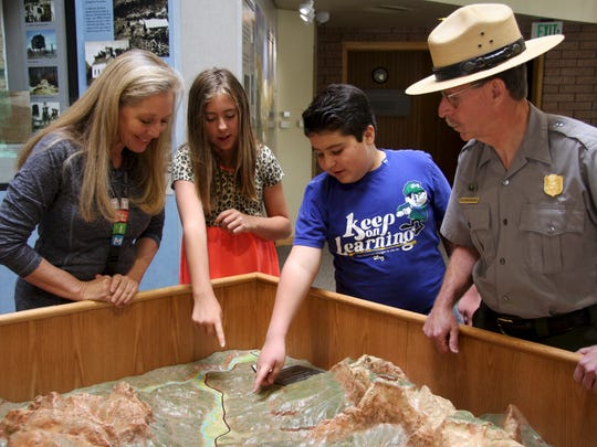 Springdale Elementary School students look at a display with Principal Chris Snodgress (left) and Zion National Park Superintendent Jeff Bradybaugh.