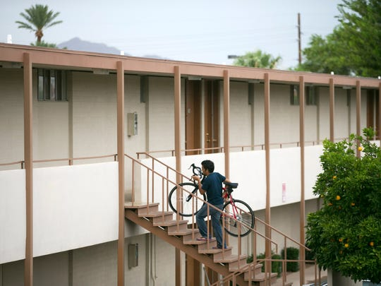 A man carries a bike towards an apartment at University