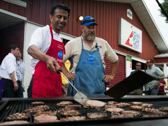 Republican presidential hopeful Gov. Bobby Jindal flips pork burgers with David Moody from the Pork Tent committee at the Iowa Pork Tent during the Iowa State Fair on Saturday, August 22, 2015.
