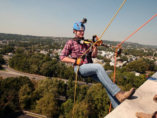 Reporter Michael Izzo rappels down a 10-story building
