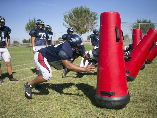 Perry High defensive lineman Saxton Simmons (center) during football practice at Perry High School in Gilbert on Tuesday, September 29, 2015.