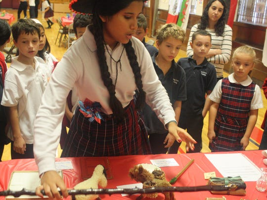 Mahia Rusul, eighth-grader at Holy Savior Academy, South Plainfield, shows third-graders a walking stick from Ireland during Heritage Day Nov. 6. The day's activities were organized by eighth-grader Grace Metz, a Girl Scout cadette, as part her project to earn the silver award, the highest award for a cadet. Rusul was one of seven students who helped Metz with the project.