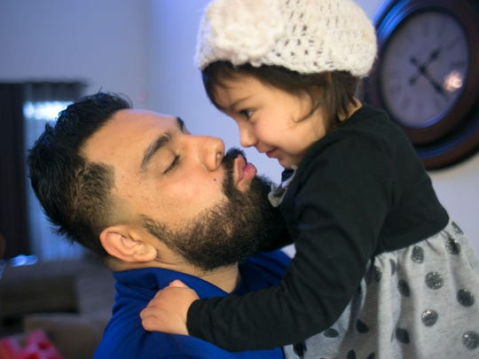 Eddie Martinez gives his daughter, Natalia Martinez, 2, a kiss, before he heads off to work from their Phoenix home on Friday, December 18, 2015.