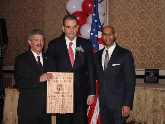 Westchester County Public Safety Commissioner George Longworth, center, is presented a Westchester County Crime Stoppers  recognition awards by chairman of the organization Derickson Lawrence, right, and Irvington Police Chief Michael Cerone, left, at the organization's fifth annual dinner on Friday, Feb. 5, 2016.