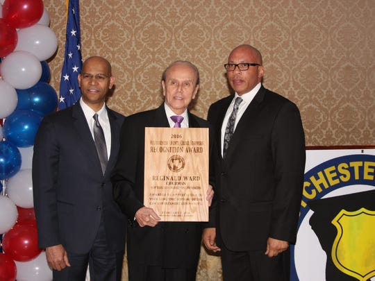 Former Mount Vernon Deputy Police Commissioner Reginald Ward, center, is presented a Westchester County Crime Stoppers  recognition awards by chairman of the organization Derickson Lawrence, left, and former Mount Vernon Police Commissioner Terrance Raynor at the organization's fifth annual dinner on Friday, Feb. 5, 2016.