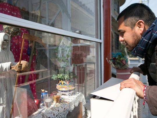 A teacher looks at a shrine of La Santa Muerte in Mexico in February 2016. The female folk saint is opposed by the Catholic Church and is believed to protect people from death.