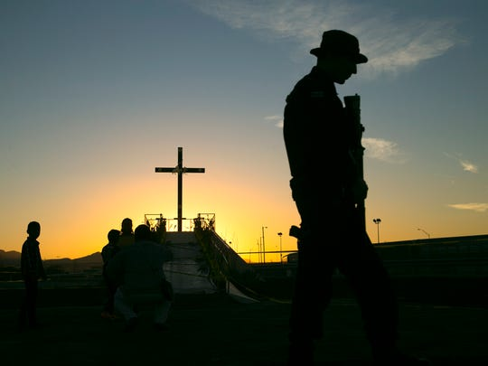 A Mexican police officer stands guard near a cross at a praying platform on the banks of the Rio Grande River near the fairgrounds in Juarez, Mexico, on Tuesday evening, Feb. 16, 2016.