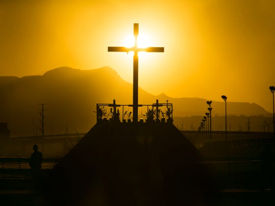 The sun sets on a cross at a praying platform on the