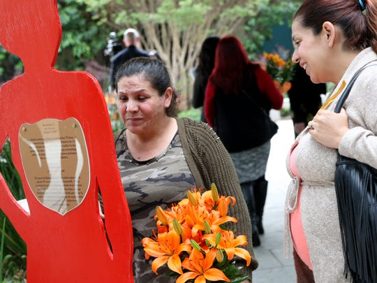 Edith Ruiz of Salinas reviews information about a victim on a wooden cut-out. Ruiz lost her son Ernesto Martinez, 35, in October.