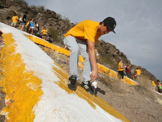 A.J. Whelan,  ASU student, helps paint  the letter