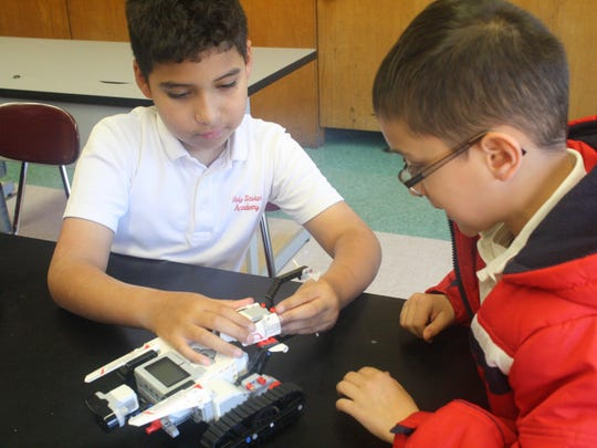 Marvin Mont, left, fifth grader at Holy Savior Academy, South Plainfield, works with Matthew Sidun, third grade, to build a robot with Legos as part of the school's newly created Robotics Club.