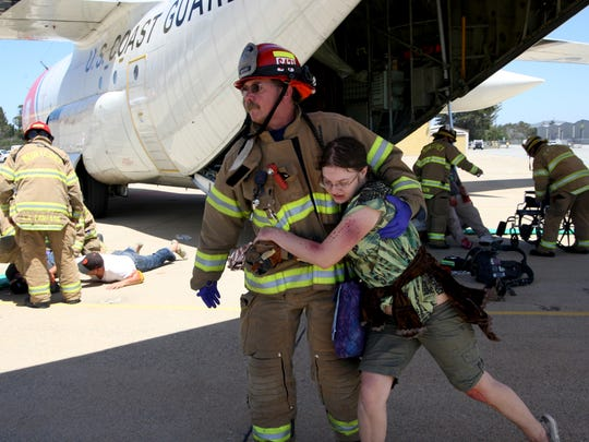 """A firefighter helps a """"patient"""" to safety during a plane crash simulation emergency response drill on Tuesday."""