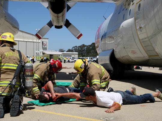 """Firefighters respond to """"patients"""" during a plane crash simulation as part of an emergency response drill at the Monterey Regional Airport on Tuesday."""