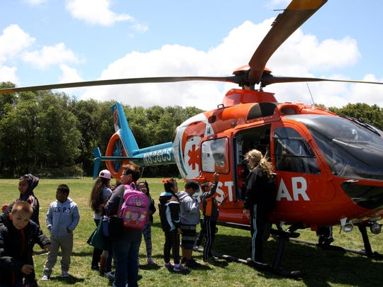 Children climb into an air ambulance during the EMS Week celebration on Friday.