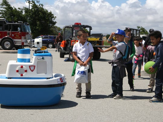 "Children play with the U.S. Coast Guard's ""Coastie"" the Tugboat."