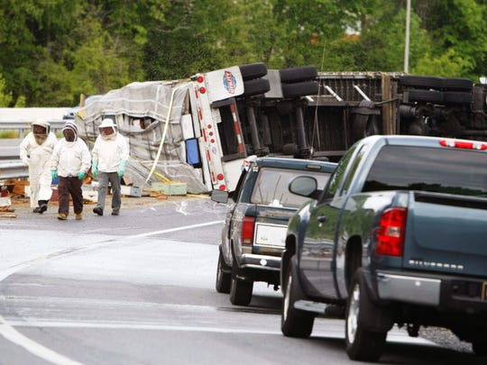 Beekeepers view damage after a truck rollover released millions of bees south of Newark on May 20, 2014. A judge has refused to dismiss a lawsuit related to the clean up.