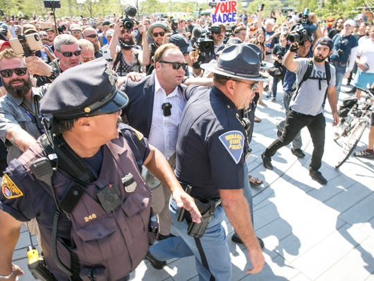 Police block Alex Jones from protesters outside the