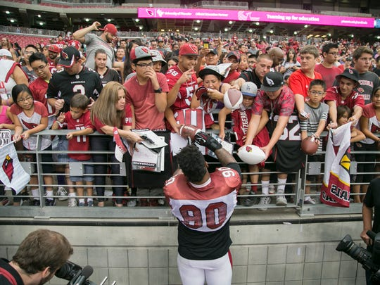 Darnell Dockett signs autographs for Cardinals fans during the 2014 Fan Fest in Glendale.