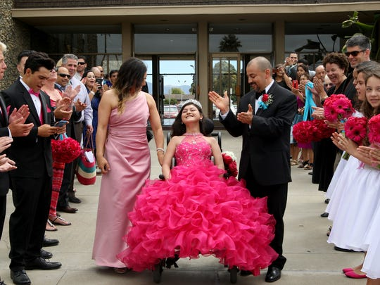 A crowd applauds as Maribel, Karizma and Edgar Vargas leave the church on the day of her quinceañera.