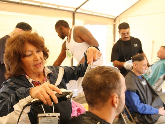 Volunteer Maria E. Rosales cuts Salinas resident Lucas Steele's hair during the Monterey County Homeless Stand Down for Homeless Veterans on Saturday.