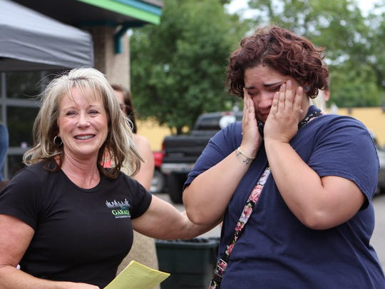 An emotional Jaleane Thomas of Highland Township wipes away tears after receiving a set of car keys and a big hug from Karen Wielkopolan, owner of Milford's Downtown Garage.