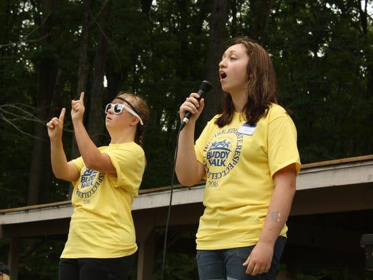 Amanda Girnis, 24, of Binghamton, interprets the Star Spangled Banner in sign-language for singer Jessica Kennis, 16, of Endwell.