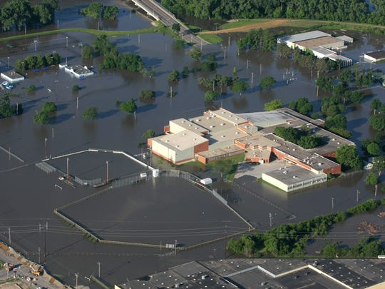 The North High School campus is flooded while workers build an emergency levee in an effort to hold back floodwater along the west edge of Second Avenue in June 2008.