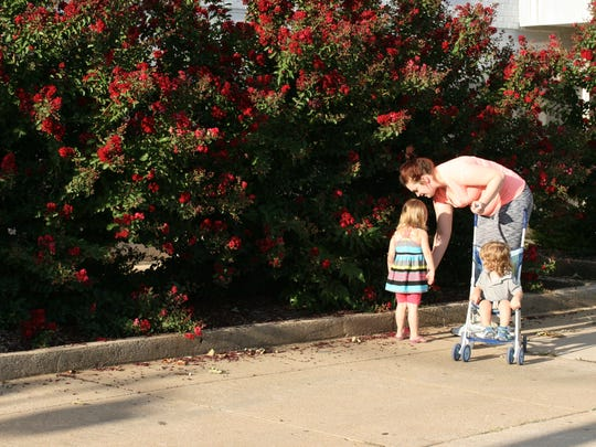 Joni Canada takes a walk with her two youngest children near the Harmony House shelter in Springfield, where they reside.