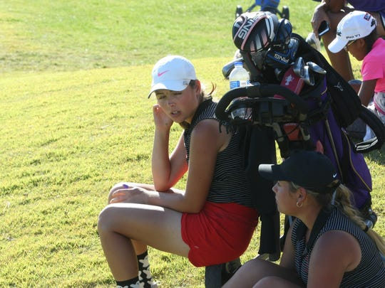 Rossview's Catherine Caudill (left) and sister Caroline sit watching the final golfers come in onto the 18th green during the final round of the 3A state golf tournament Wednesday at WillowBrook Golf Course.