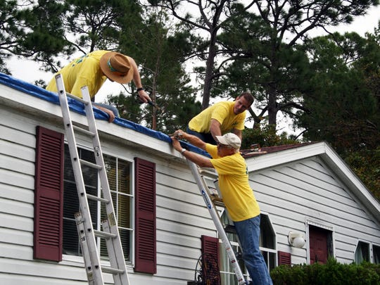 Members of a local Latter-day Saints ward put a tarp on a Melbourne home as part of a countywide post-hurricane project.