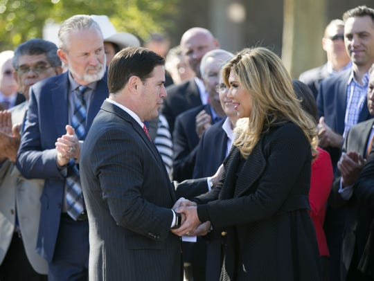 Arizona Gov. Doug Ducey shakes hands with the governor