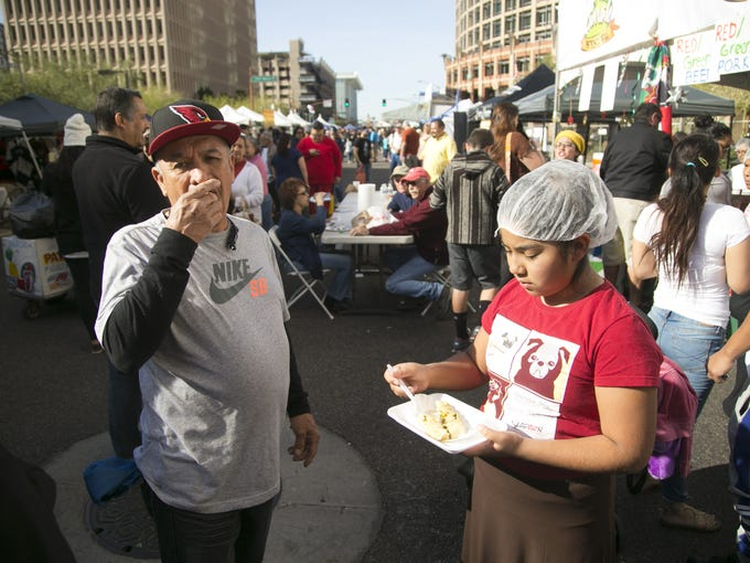 Raul Ramirez of Phoenix eats a free sample of tamale