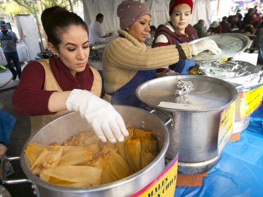 Elvira Hernandez pulls out hot tamales from a pot to