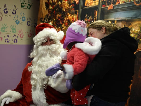 Erin Eckert, 37, holds Alexis Exckert, 1, both of Endwell, as Alexis meets Santa during Christmas in the Park in 2016.