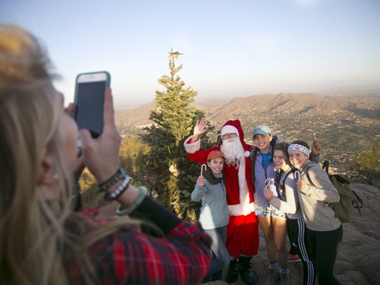 "John Cressey of Scottsdale, the ""Camelback Santa,"" poses for photos with hikers by the Christmas tree on the summit of Camelback Mountain in Phoenix on Dec. 17, 2016. Cressey climbs to the top of Camelback a dozen times in December through Christmas taking pictures with people on the summit and giving them candy canes. He has been doing this for four years."