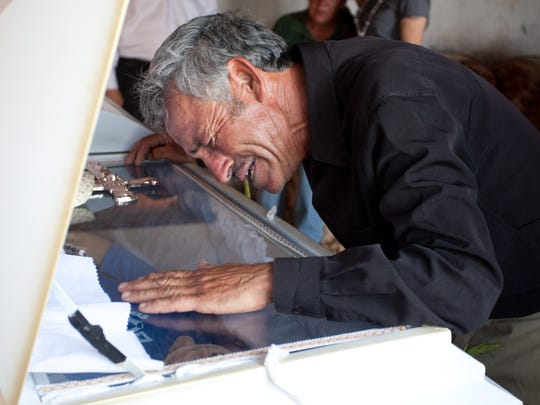 Overcome with grief, Jesus Librado, the father of 15-year-old Sergio Adrián Hernández Güereca, who was shot to death by a Border Patrol agent Monday, June 7, 2010, weeps over his son's coffin at the family home in Juarez. The incident took place after the boy and some friends were accused of throwing rocks at Border Patrol agents.