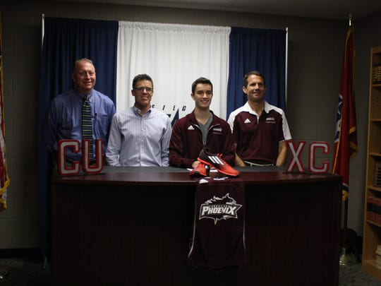 Siegel cross country and track standout Titus Williams recently signed with Cumberland University. Pictured (l-r) are Siegel Principal Larry Creasy, Siegel Cross Country Coach Phil Young, Titus Williams, and Cumberland University Coach Jim Seckel.