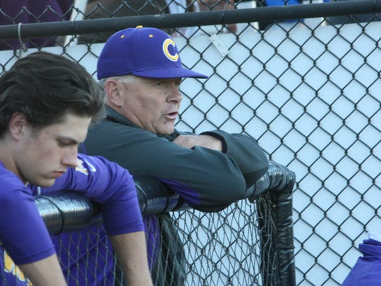 Clarksville coach Brian Hetland leans over the fence
