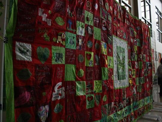 A quilt displayed at Saturday's Lyme disease conference honored those battling Lyme or other tick-borne illnesses with red squares, and those who died of Lyme or tick-borne illnesses with green squares.